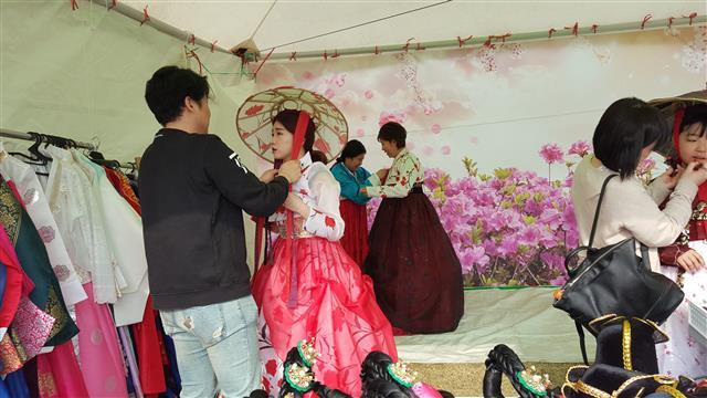 진달래축제장을 찾은 여성들이 진달래 무늬로 장식된 전통 모자를 써 보고 있다.