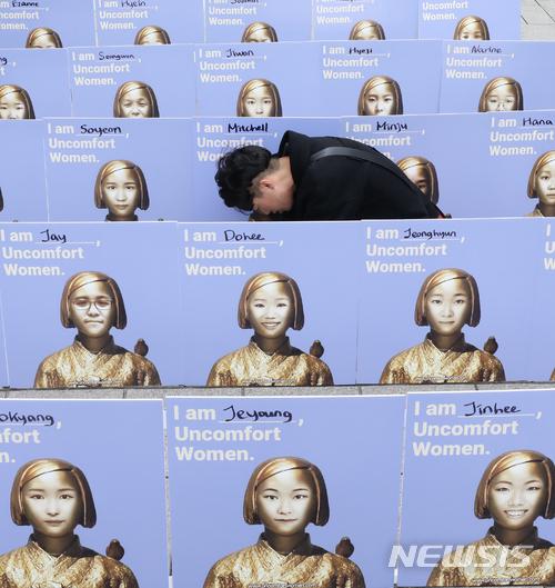 【서울=뉴시스】권현구 기자 = 지난달 7일 오후 서울 종로구 옛 일본대사관 앞에서 열린 일본군 위안부 문제 해결을 위한 1325차 정기 수요시위에서 관계자들이 수요집회에 참석하지 못하는 시민들의 얼굴을 소녀상과 합성하는 'UNCOMFORT WOMEN' 퍼포먼스를 하고 있다. 2018.03.07. stoweon@newsis.com