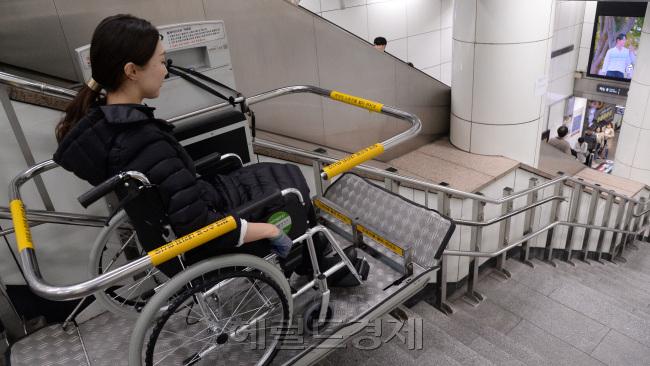 서울 광화문역에 설치된 휠체어 리프트를 탑승하고 내려가는 모습. [사진=정희조 기자/ checho@heraldcorp.com]