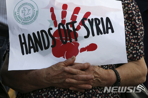 【니코시아=AP/뉴시스】16일(현지시간) 키프로스 니코시아에 위치한 미국 대사관 밖에서 미국 주도의 시리아 화학무기 시설 공습을 규탄하는 시위가 벌어지고 있다. 한 시위자가 '시리아에서 손 떼라'는 문구가 적힌 종이를 들고 있다. 2018.4.17.