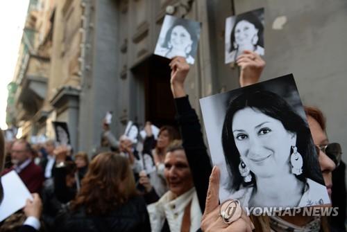 16일(현지시간) 몰타 수도 발레타에서 탐사전문 기자 다프네 카루아나 갈리치아의 암살 6개월을 맞아 그녀의 사진을 들고 추모하고 있는 사람들 [AFP=연합뉴스]