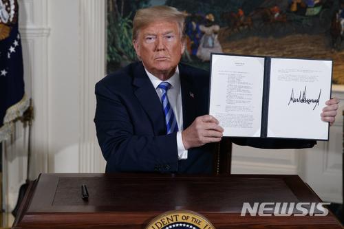 """【워싱턴=AP/뉴시스】도널드 트럼프 미국 대통령이 8일(현지시간) 미국의 이란 핵합의(JCPOA·포괄적 공동행동계획) 탈퇴를 공식 선언했다. 트럼프 대통령은 이날 백악관에서 가진 기자회견을 통해 """"이란의 핵 합의는 거짓이었다는 분명한 증거를 지니고 있다. 이란은 핵무기 프로그램을 계속 추진해 왔다""""라고 말했다. 트럼프 대통령령이 이날 JCPOA 탈퇴를 선언하는 각서에 서명한 뒤 이를 들어보이고 있다. 2018.05.09."""