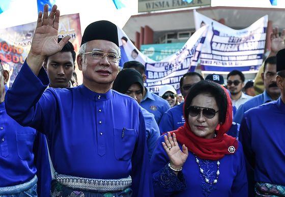지난 4월28일 선거 등록에 나선 말레이시아 나집 라작 총리와 그의 부인 로스마 만소르 여사가 시민들에게 손을 흔들고 있다. 지난 9일 치러진 총선에서 패배한 나집 전 총리는 당국으로부터 출국 금지 조치를 받았다. [AFP=연합뉴스]