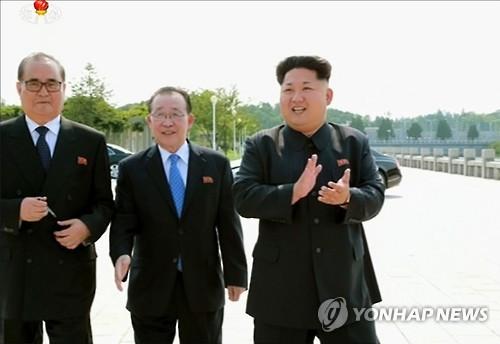 외교관들 만나 박수 치는 김정은 (서울=연합뉴스) 김정은 국방위원회 제1위원장이 '대사회의'에 참석한 북한 외교관들과 함께 기념사진을 찍었다고 15일 조선중앙통신이 보도했다. 최근 해외 주재 북한 중간 간부들의 동요가 커지고 있는 가운데 김정은 제1위원장이 이례적으로 이들을 만나 사진을 찍으며 '군기 잡기'에 나선 것이라는 분석이 나온다. 사진은 박수를 치는 김정은 제1위원장과 리수용 외무상(왼쪽), 김계관 외무성 제1부상(가운데)의 모습을 조선중앙TV 화면에서 캡처한 것. 2015.7.15