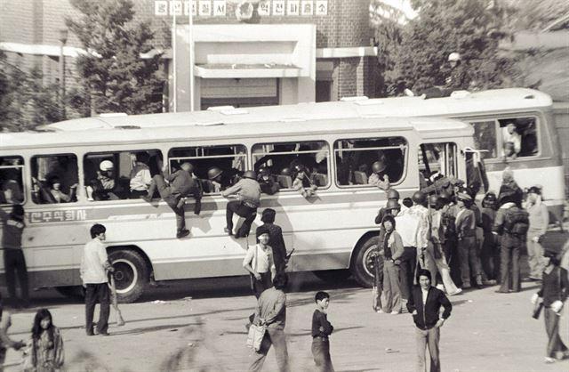 20일 광주 송정리역 광장에서 소총으로 무장한 시민군이 금남로로 향하는 버스에 앞다투어 올라타고 있다.