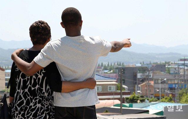한국에서 태어나 이른바 '그림자 아이'로 자라난 페버 씨(오른쪽)가 지난해 6월 충북 청주 외국인보호소에서 풀려난 뒤 어머니 조널 씨와 함께 먼 산을 바라보고 있다. 청주=김재명 기자 base@donga.com