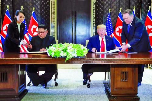 도널드 트럼프 미국 대통령(오른쪽)과 김정은 북한 국무위원장이 12일 싱가포르 센토사섬 카펠라 호텔에서 역사적인 공동성명에 서명하기 위해 나란히 앉아 있다. 마이크 폼페이오 국무장관과 김여정 노동당 제1부부장이 각각 두 정상 옆에서 서명을 돕고 있다. AP뉴시스