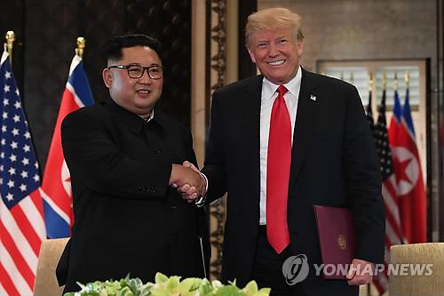 (싱가포르 AFP=연합뉴스) 역사적 첫 북미정상회담이 열린 12일(현지시간) 싱가포르 센토사 섬 카펠라호텔에서 미국 도널드 트럼프 대통령(오른쪽)과 북한 김정은 국무위원장이 공동합의문에 서명한 뒤 악수하고 있다.