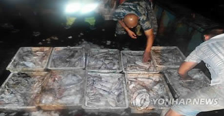 중국 운반선에 불법 적재 중인 오징어 (목포=연합뉴스) 해양수산부 서해어업관리단은 지난 13일 새벽 충남 보령시 오천면 외연도 서방 약 140km 해상에서 84t급 중국 어획물운반선 Y호를 조업일지 부실기재 혐의 등으로 나포했다고 14일 밝혔다. 사진은 중국 운반선 선원들이 조업일지 기록을 속이거나 할당된 어획량을 초과한 오징어를 배에 불법으로 적재한 모습. 2017.9.14 [서해어업관리단 제공=연합뉴스]      areum@yna.co.kr