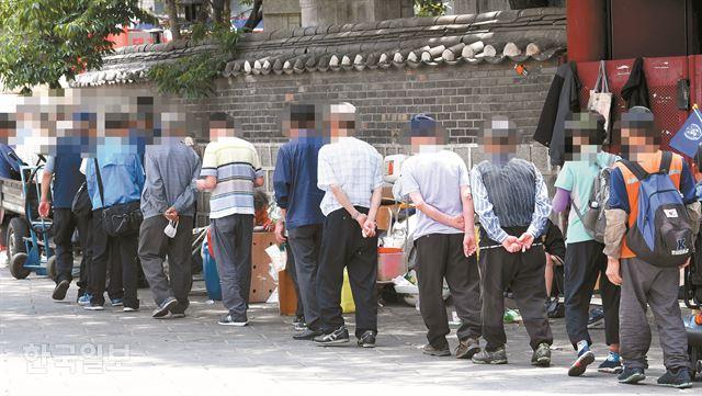 지난 5일 서울 종로구 탑골공원에서 노인들이 무료급식 차례를 기다리고 있다. 배우한 기자