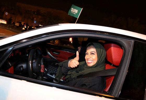 사우디 여성 운전자가 24일(현지시간) 새벽 알 코바르 시내에서 운전하며 엄지 손가락을 펴보이 고 있다. [로이터=연합뉴스]