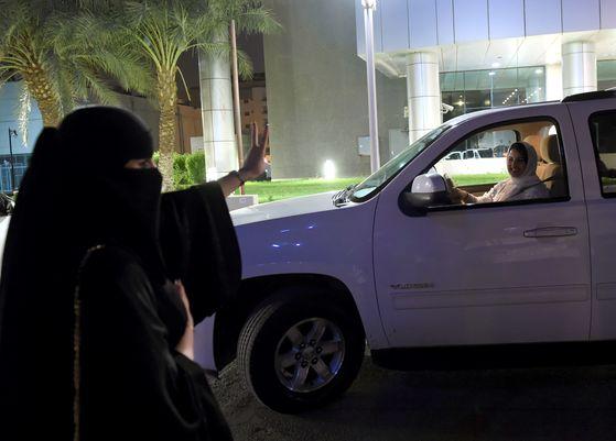 한 사우디 여성이 24일(현지시간) 리다아 중심 도로에서 운전하는 사마르 알 모겐에게 손으로 'V' 표시를 하며 응원하고 있다. [AFP=연합뉴스]