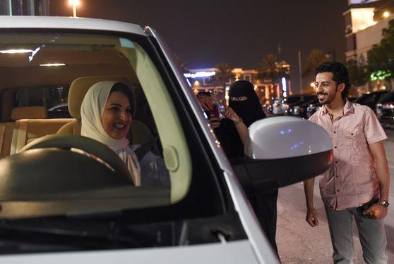 사우디 한 여성과 남성이 24일(현지시간) 리디야 시내를 처음으로 운전한 사마르 알 모겐을 응원하고 있다. [AFP=연합뉴스]
