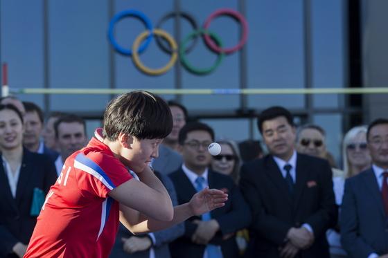 23일 스위스 로잔에서 열린 IOC 올림픽데이 행사에 북한의 김송이가 서브를 시도하고 있다. 오른쪽은 북한 김일국 체육상. [EPA=연합뉴스]
