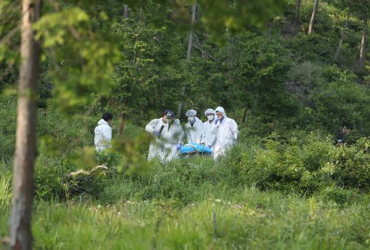 24일 전남 강진군 도암면 한 야산에서 경찰이 실종된 여고생으로 추정되는 시신을 수습해 옮기고 있다. 연합뉴스