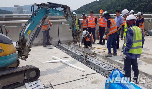 【부산=뉴시스】 하경민 기자 = 지난 24일 부산울산고속도로 부산방향 기장2터널 앞 만화교 교각에서 톱니 모양의 신축이음장치가 도로면으로 돌출돼 차량 45대의 타이어가 훼손하는 사고가 났다.25일 사고현장에서 한국도로공사 등이 이틀째 만화교 신축이음장치 복구작업을 펼치고 있다. 2018.06.25. (사진=부산경찰청 제공)yulnetphoto@newsis.com