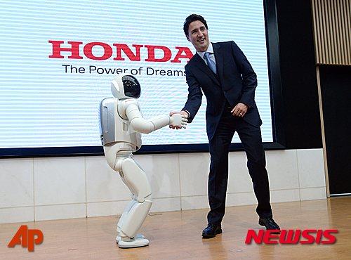 【도쿄=AP/뉴시스】일본을 방문한 저스틴 트뤼도 캐나다 총리가 24일 도쿄 혼다자동차 본사에서 로봇 아시모와 악수하고 있다. 2016.05.24