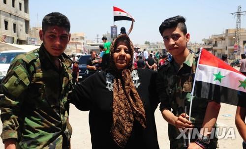 시리아군을 환영하는 남부 다라 외곽 마을의 주민들 [신화=연합뉴스]