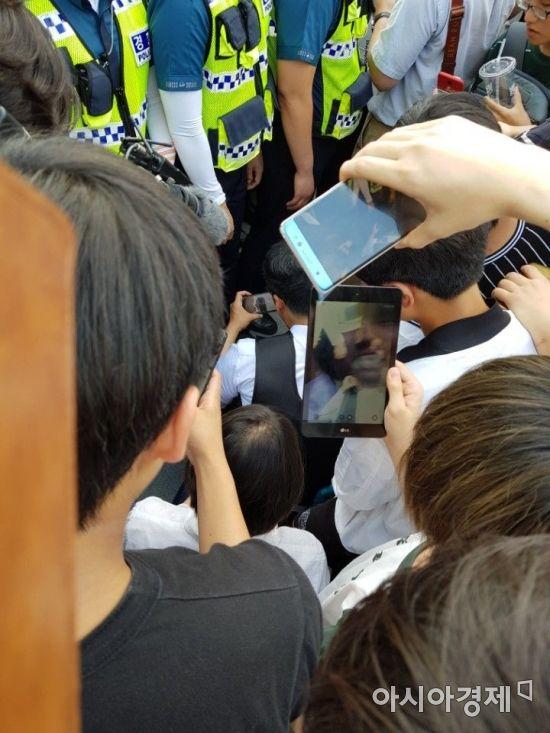 인터넷 방송인 액시스마이콜이 7일 오후 4시께 경찰 통제선을 뚫고 집회 현장에 진입하려다 제지당하자 바닥에 앉아 개인 영상을 생중계하며 부당함을 호소하고 있다.(사진=문혜원 기자)