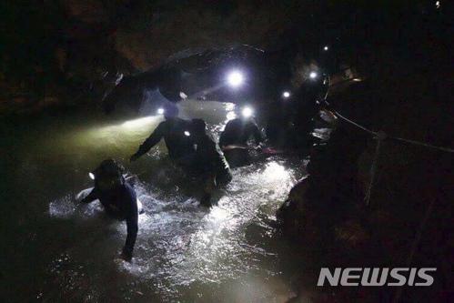 【매사이(태국 치앙라이주)=AP/뉴시스】태국 북부 치앙라이주의 동굴에서 2일 구조대원들이 지난달 23일 실종된 어린이 축구팀원 12명과 축구 코치를 찾기 위해 물 속을 수색하고 있다. 열흘 간 행방불명이던 이들 13명은 이날 영국 구조대에 의해 전원 생존해 있는 것이 확인됐다.    2018.7.3