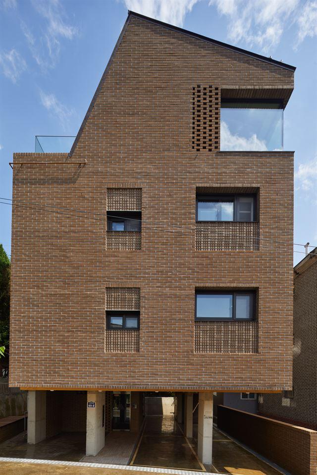 골목 쪽에서 본 닮담집. 2,3층엔 임대세대 4가구가 살고 꼭대기층엔 주인 부부가 산다. 노경 건축사진작가