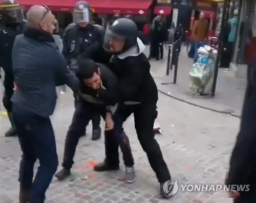 지난 5월 1일 파리 시내 노동절 집회에서 경찰용 헬멧을 쓰고 시위대로 보이는 시민을 제압하는 알렉상드르 베날라  [AP=연합뉴스]