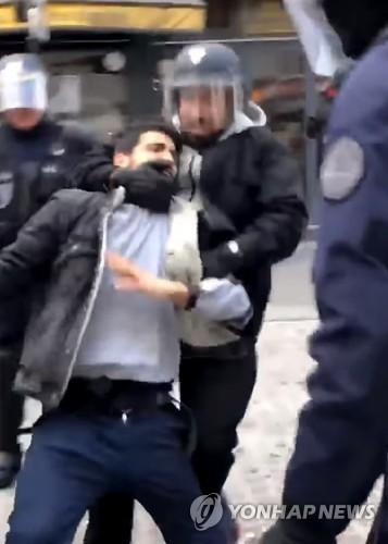 지난 5월 1일 파리 시내 노동절 집회에서 경찰용 헬멧을 쓰고 시위대로 보이는 시민을 제압하는 알렉상드르 베날라  [AFP/ Taha Bouhafs 제공=연합뉴스]