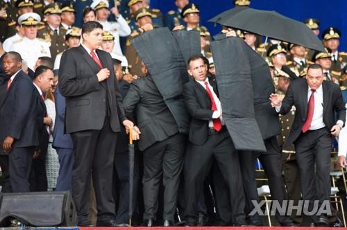 4일(현지시간) 마두로 베네수엘라 대통령의 연설 도중 인근 상공에서 폭발물이 터지자 경호원들이 방탄 장비로 마두로 대통령을 둘러싸고 있다.[신화=연합뉴스]