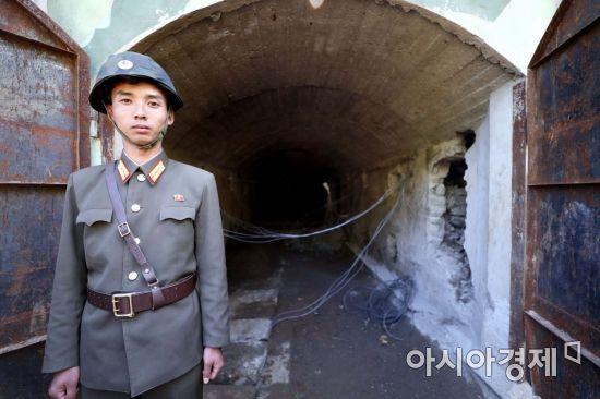 24일 북한 핵무기연구소 관계자들이 함경북도 길주군 풍계리 핵실험장 폐쇄를 위한 폭파 작업을 했다. 북한 군인이 핵실험장 3번 갱도 앞을 지키고 있다./사진공동취재단