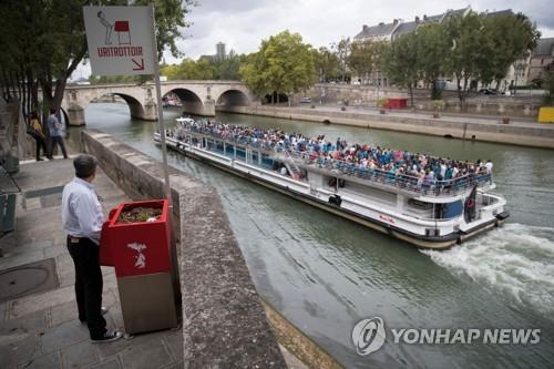 13일(현지시간) 파리 센강 인근에 설치된 공중 소변기 앞에 서 있는 한 남성[AFP=연합뉴스]