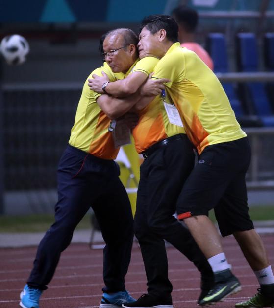 베트남 축구대표팀 스태프들이 아시안게임에서 베트남을 사상 첫 4강에 올려 놓은 박항서 감독(가운데)을 끌어안고 있다. [연합뉴스]