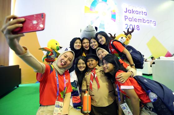 2018 자카르타-팔렘방 아시안게임 자원봉사자들이 2일 인도네시아 자카르타 컨벤션센터에 마련된 메인 프레스센터에서 한 어린이와 기념촬영을 하고 있다. 자카르타=김성룡 기자