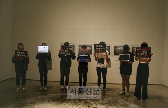 지난 8일 갤러리 현대를 찾은 동물권 활동가들이 이강소 화백의 작품을 둘러싸고 '전시 중단을 요구하며' 시위를 벌이고 있다. (동물권 단체 MOVE 제공)