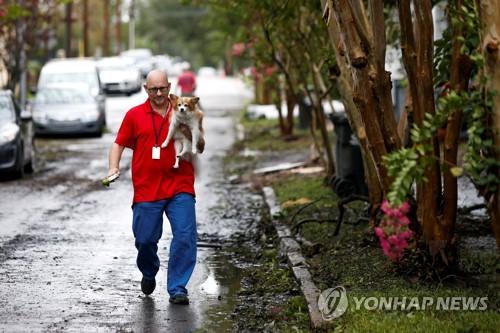 허리케인 '플로렌스' 때 한 남성이 강아지를 안고 걸어가고 있는 모습 기사 본문 내용과는 무관한 자료사진 [로이터=연합뉴스]