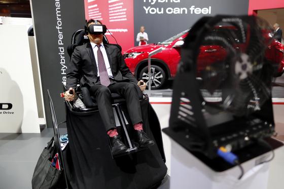 2일 한 관람객이 일본 혼다 전시장에 마련된 버추얼 콕핏 장치에 앉아 운전체험을 하고 있다.[EPA=연합뉴스]