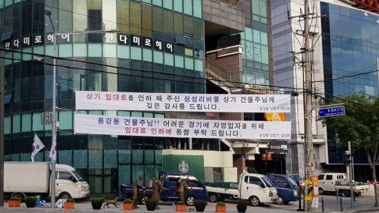 용강동 상점가 상인회에서 건물주들에 임대료 인하를 요구하는 플래카드를 내걸었다.