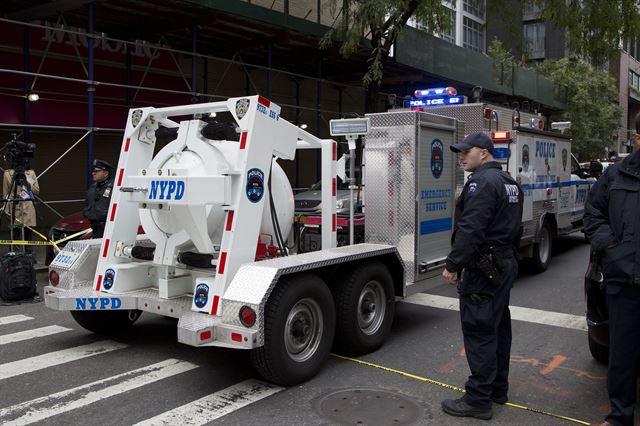 26일 미국 뉴욕 경찰이 맨해튼에서 발견된 폭탄으로 의심되는 소포를 완전봉인차량에 싣고 트럭으로 이동하고 있다. 뉴욕=AP 연합뉴스