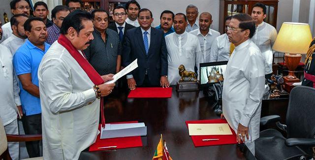 26일 마이트리팔라 시리세나(오른쪽) 스리랑카 대통령이 마힌다 라자팍사(왼쪽) 신임 총리에게 임명장을 전달하고 있다. 콜롬보=AP 연합뉴스