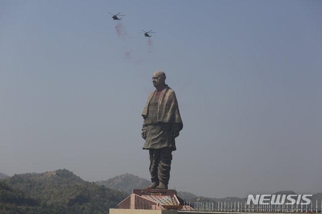 【나라마다(구자라트)=AP/뉴시스】31일 인도 구자라트 주 나라마다에서 세계에서 가장 높은 인도 동상 '통일의 동상' 공개식이 개최돼, 인도 공군이 헬리콥터로 상공에서 꽃가루를 뿌리며 축하하고 있다. 2018.10.31