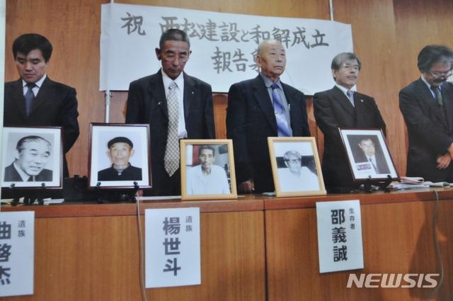 【서울=뉴시스】중국인 징용 피해자들이 2009년 11월 일본 기업 니시마츠건설 측과 사과 및 배상 방안에 합의한 뒤 '화해성립 보고집회'를 갖는 모습. 단상 위에 놓인 액자 속 인물들은 피해자 중 이미 사망한 이들이다. 뉴시스 자료사진.