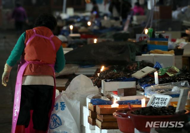 【서울=뉴시스】이영환 기자 = 수협이 노량진 수산시장 구시장 전역에 단전과 단수를 진행한지 하루 지난 6일 오전 서울 동작구 노량진 수산시장 구시장이 어둑어둑한 가운데 상인들이 촛불을 켜고 장사를 하고 있다. 2018.11.06.  20hwan@newsis.com