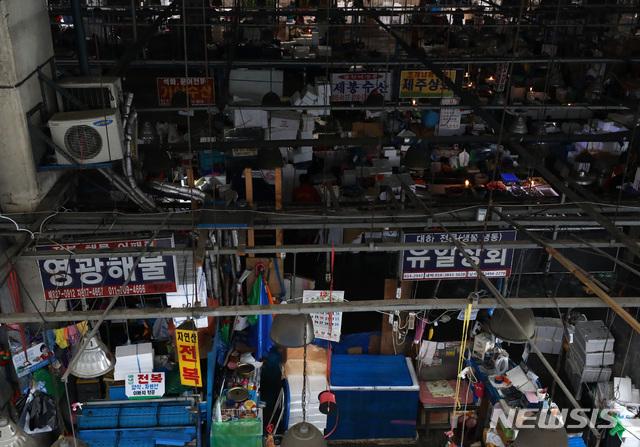 【서울=뉴시스】이영환 기자 = 수협이 노량진 수산시장 구시장 전역에 단전과 단수를 진행한 지 하루 지난 6일 오전 서울 동작구 노량진 수산시장 구시장이 어둑어둑한 가운데 상인들이 촛불을 켜고 장사를 하고 있다. 2018.11.06.  20hwan@newsis.com