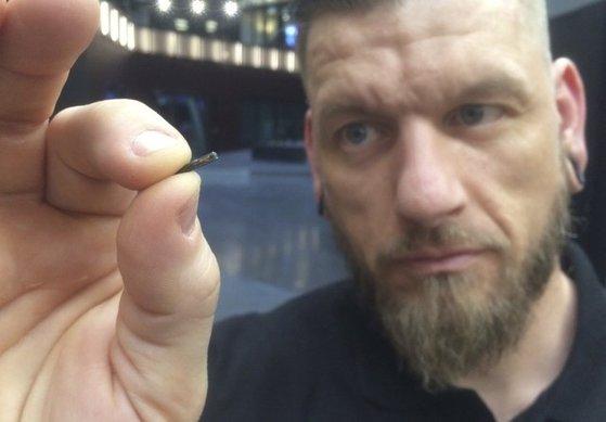 스웨덴 바이오핵스의 직원이 몸속에 이식되는 생체 칩을 들어 보이고 있다. [AP=연합뉴스]