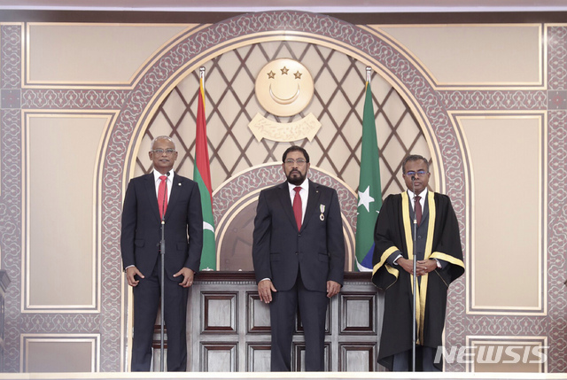 【말레=AP/뉴시스】 17일(현지시간) 몰디브 말레의 국립경기장에서 야권 연대의 이브라힘 모하메드 솔리(가운데) 후보가 대통령 취임 선서를 하고 있다. 이날 취임식에는 수천 명의 시민들이 축하를 위해 참석한 것으로 알려졌다. 2018.11.17.