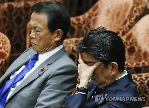 아베 신조 일본 총리(오른쪽)가 아소 다로 부총리 겸 재무상(왼쪽)과 함께 중의원 예산위원회에 출석해 고개를 숙인 채 얼굴을 손으로 가리고 있는 모습 [EPA=연합뉴스 자료사진]