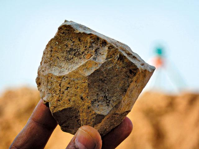 올도완 석기를 연구자가 들어 보이고 있다. 돌을 내리쳐 날카로운 조각(격지)을 떼어냈다. 사진 출처 사이언스