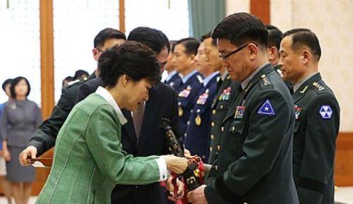 2013년 4월 박근혜 당시 대통령이 이재수 중장으로부터 진급신고를 받은 뒤 삼정도에 술을 매어주고 있다. 뉴시스