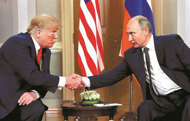 도널드 트럼프(왼쪽) 미국 대통령과 블라디미르 푸틴 러시아 대통령이 지난 7월 핀란드 헬싱키에서 정상회담 도중 악수를 나누고 있다. 헬싱키=로이터 연합뉴스