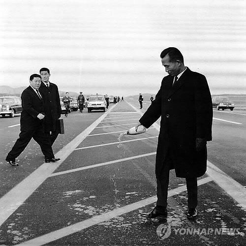 1968년 12월 21일 경인고속도로 개통식에 참석한 박정희 대통령이 노면에 샴페인을 뿌리며 기뻐하고 있다. [국가기록원 제공]