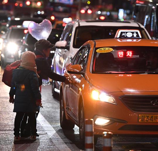 한 여성과 어린이가 성탄절 하루 전인 24일 오후 서울 종로구 종각역 인근 거리에서 차도까지 나와 택시를 잡고 있다. 권현구 기자